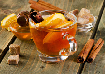 Hot tea with orange and spices on wooden background