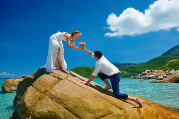 Loving couple on sea beach - a man making proposal with bouquet