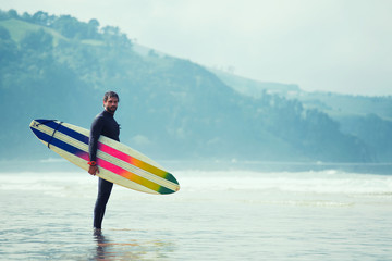 Surfer standing with surfboard with multi-colored stripes