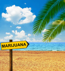 Tropical beach and direction board saying MARIJUANA