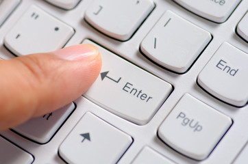 Close up Male hand finger press enter computer keyboard button