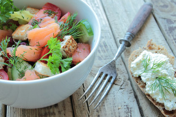 Healthy salmon salad with fresh vegetables and herbs
