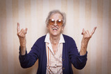 cool elder lady making rock on sign