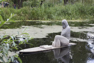 Stone sculpture of a priest on the water