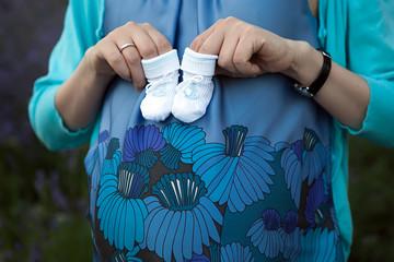 pregnant woman with tiny socks for future baby boy