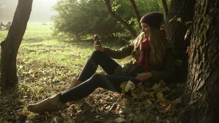 Cheerful young girl taking self picture in autumn park.