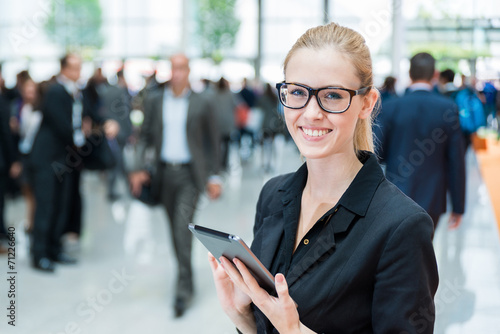 canvas print picture young business woman at a trade fair