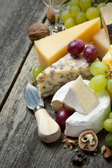 fresh cheeses, grapes and walnuts on a wooden background