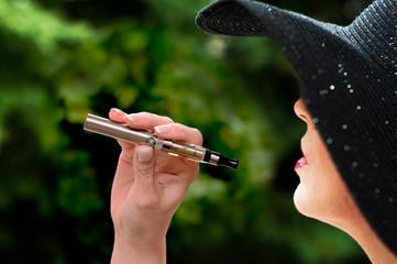 jeune femme avec chapeau avec une cigarette électronique