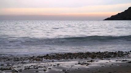 Kleine Wellen am Strand bei Sonnenuntergang