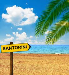 Tropical beach and direction board saying SANTORINI