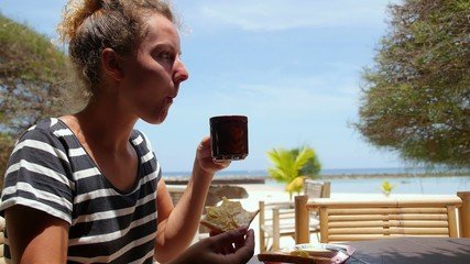 Woman Eating Toast and Drinking Coffee at Beach Cafe.