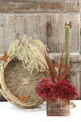 florale Herbstzeit mit Gräsern, Sedum bei Kerzenschein