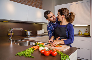 Couple hugging and preparing vegetables in the kitchen