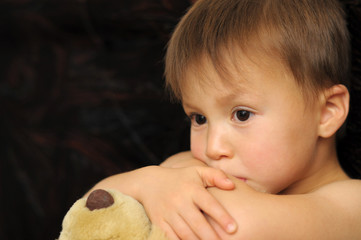 Thinking boy hugging teddy bear