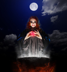 Witch with red potion and cauldron on night sky background