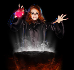 Young witch with potion and cauldron