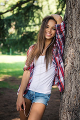 Smiling teenager portrait listening to music outdoors in a park.