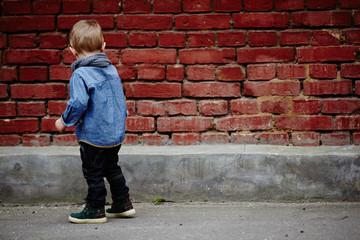 little boy near red brick wall