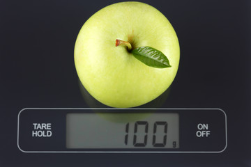 Green apple on kitchen scale