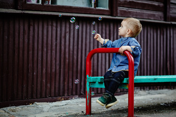 little boy catches bubbles sitting on bench