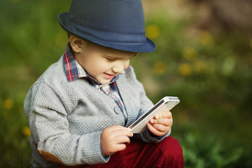 boy with phone sitting on grass