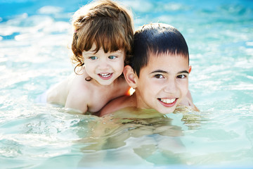 brother and sister bathe outside in pool