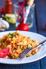 risotto with chicken and vegetables on dark wooden board