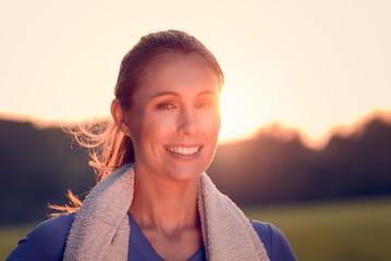 Attraktive junge Frau draußen im Sonnenuntergang