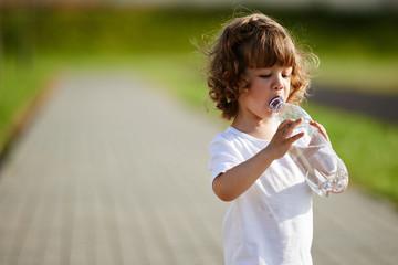 little girl drinking clean water from bottle