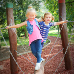 Litle friends have a fun on a garden swing.
