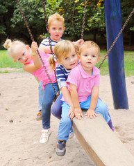 Litle kids have a fun on a garden swing.