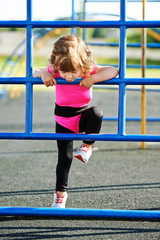 cute little girl plays on playground