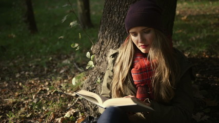 Beautiful caucasian girl reading a book in the autumn park.
