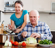 Ordinary mature couple cooking with vegetables