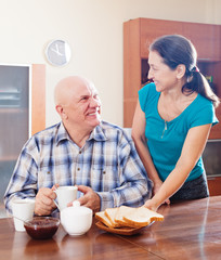 mature woman serving toast to happy  man