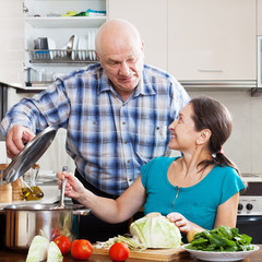 mature couple cooking food