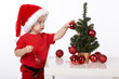boy with Santa hat decorates christmas tree