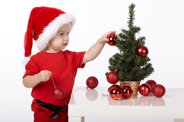 boy with Santa hat decorates christmas tree