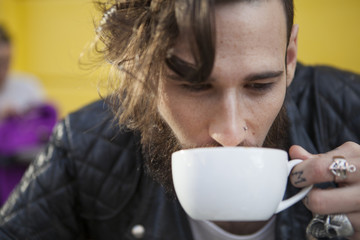 Closeup of male face with beard drinking cappucino
