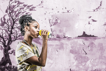 girl drinking soda in front of mural