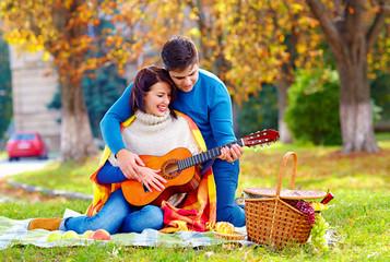 man teaching girl play a guitar on autumn picnic