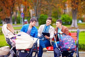 three happy fathers with buggies in city park