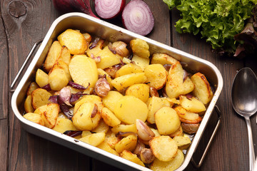 Baked potatoes in a roasting pan with garlic and onion on a wood