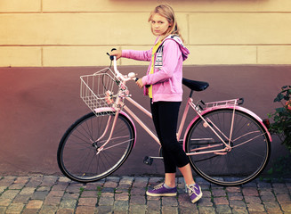 Little blond Caucasian girl in pink with bicycle, vintage toned
