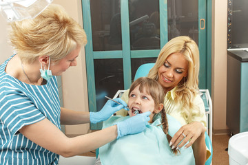 Little girl sitting in mom's lap while dentist examines her teet