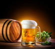 Beer barrel with beer glass on a wooden table. The dark backgrou