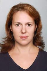 Young Caucasian woman closeup portrait. Headshot on gray