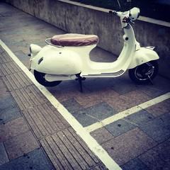 old, white motor scooter on the street