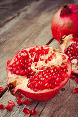 Pieces of ripe pomegranate on wooden table